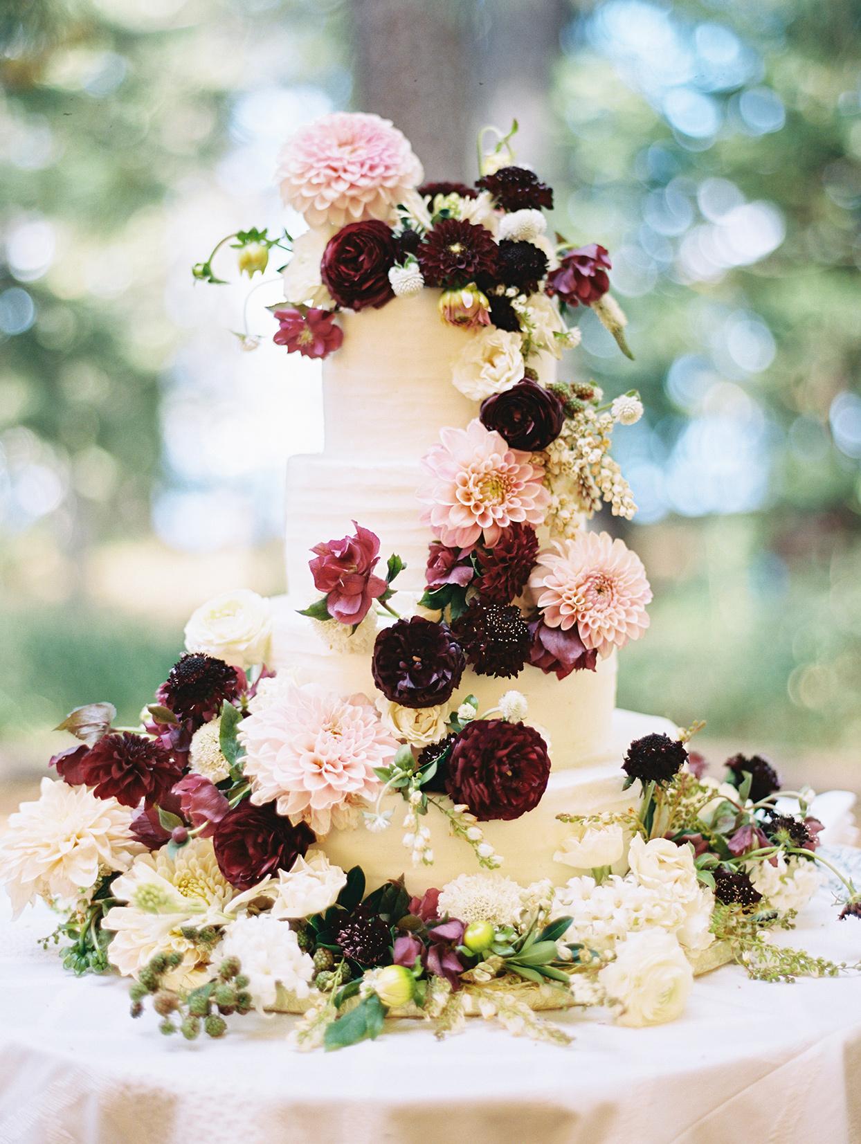 white wedding cake with garland of purple, burgundy and cream flowers