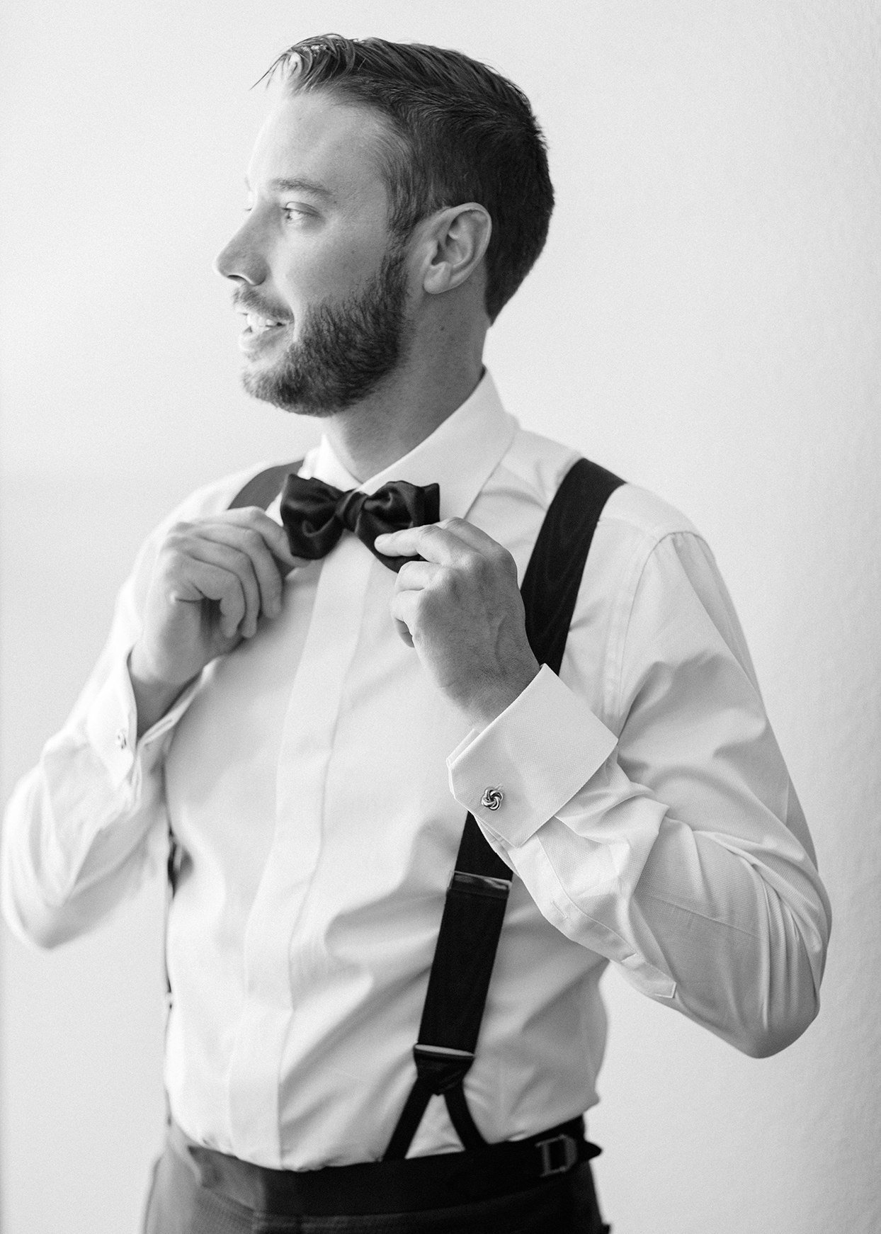 groom fixing bowtie into his wedding outfit