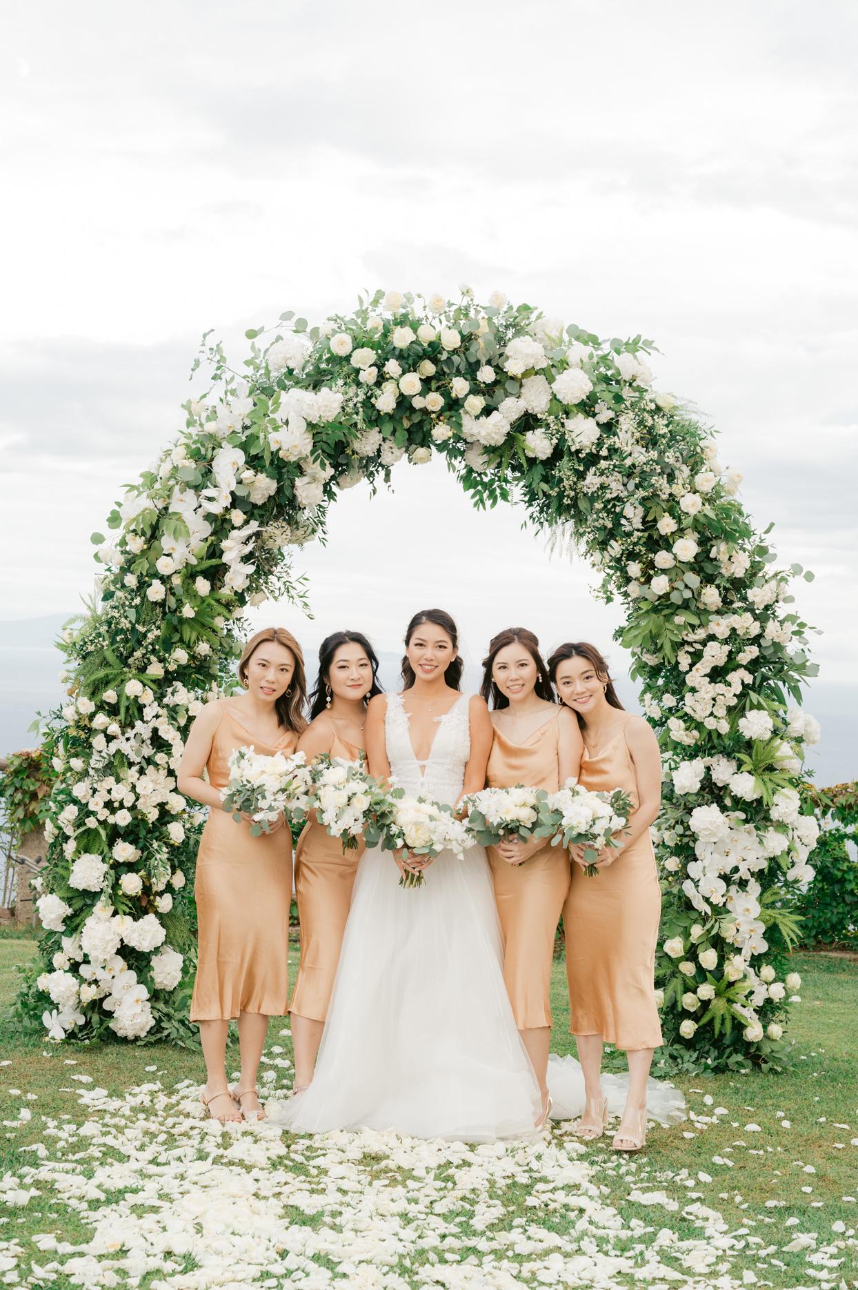bride with bridesmaids wearing tea length orange dresses under floral wedding arch