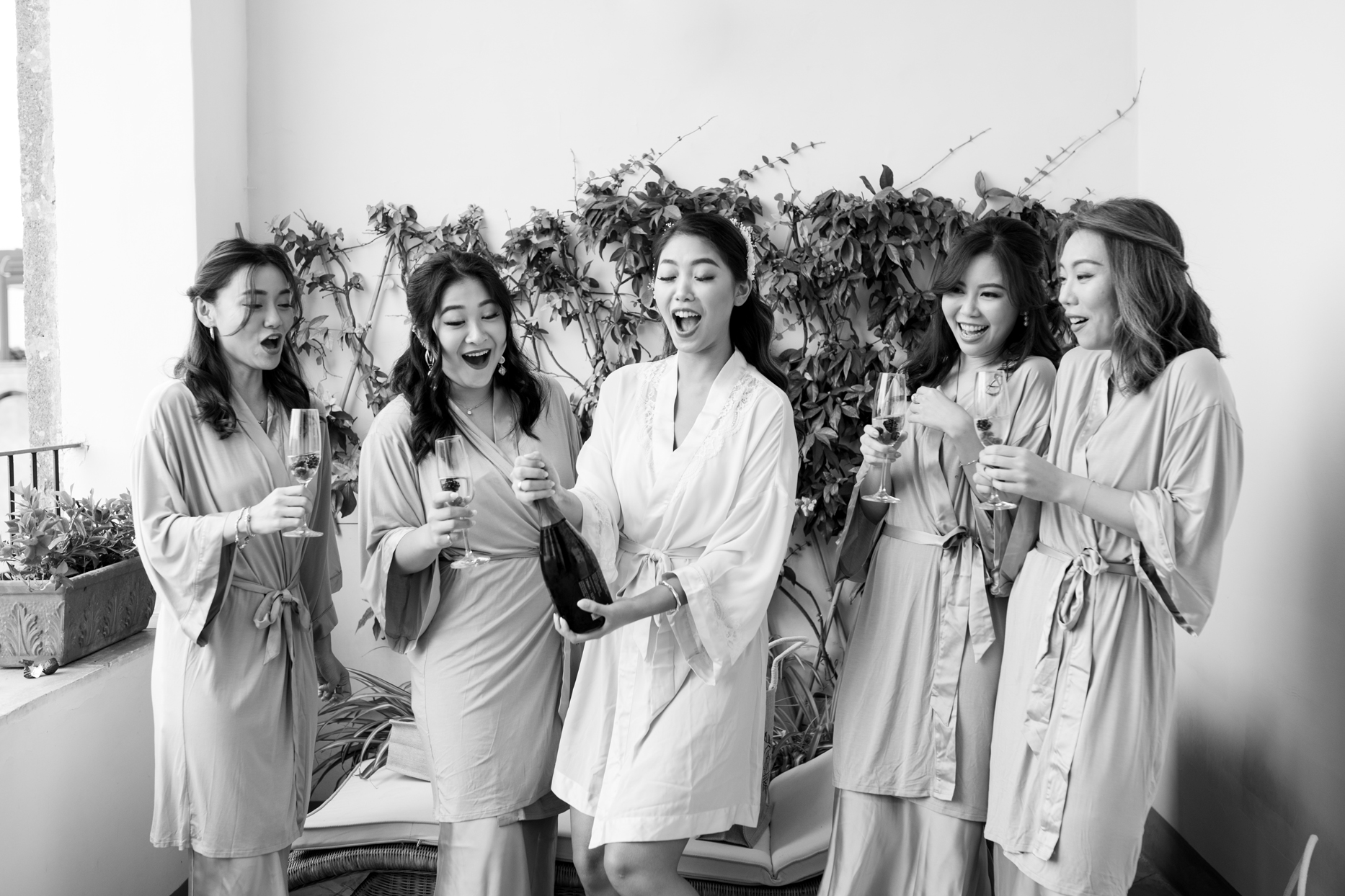 bride popping champagne bottle with bridesmaids wearing robes