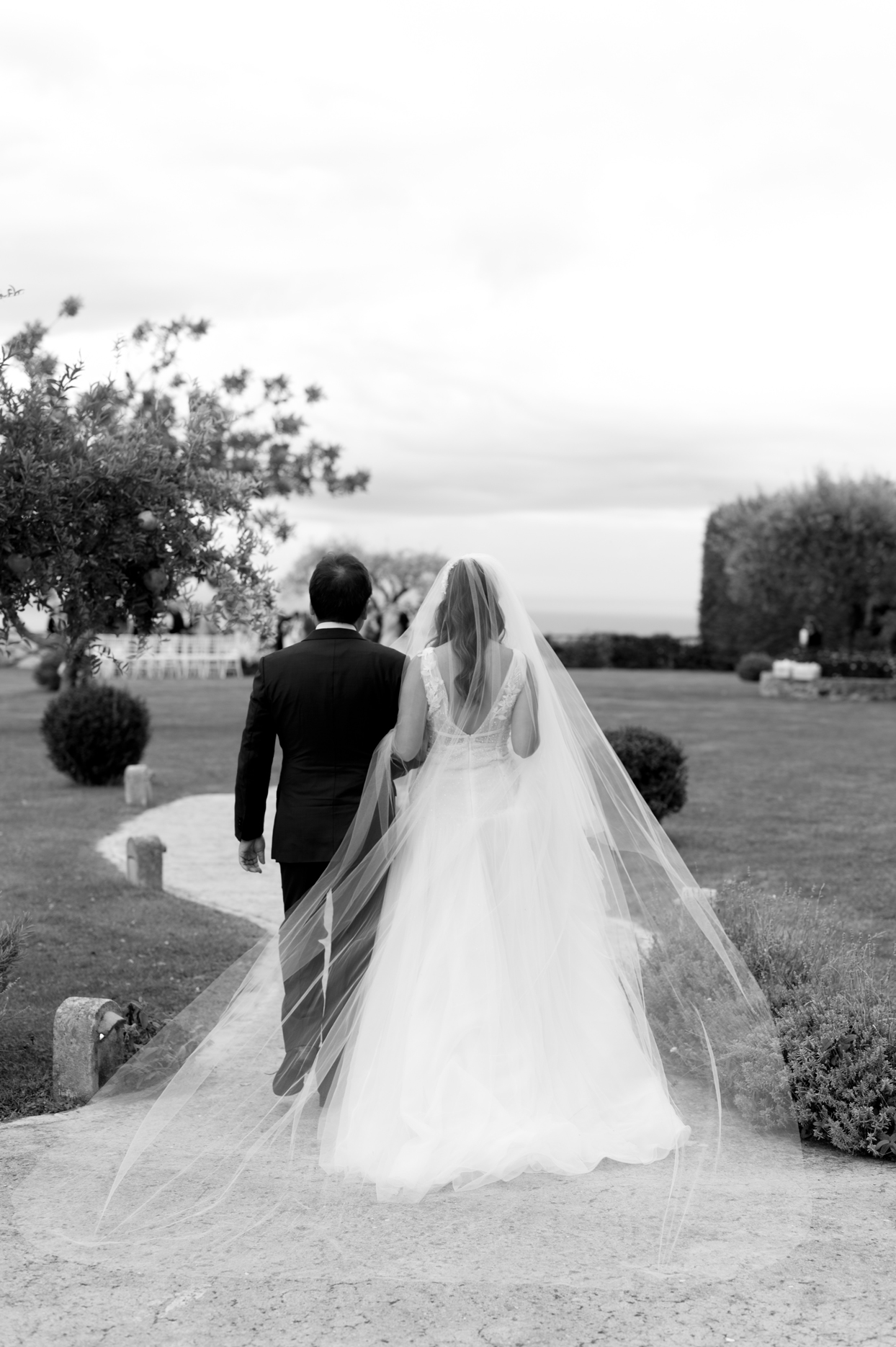 bride and father walking down path outside to wedding alter