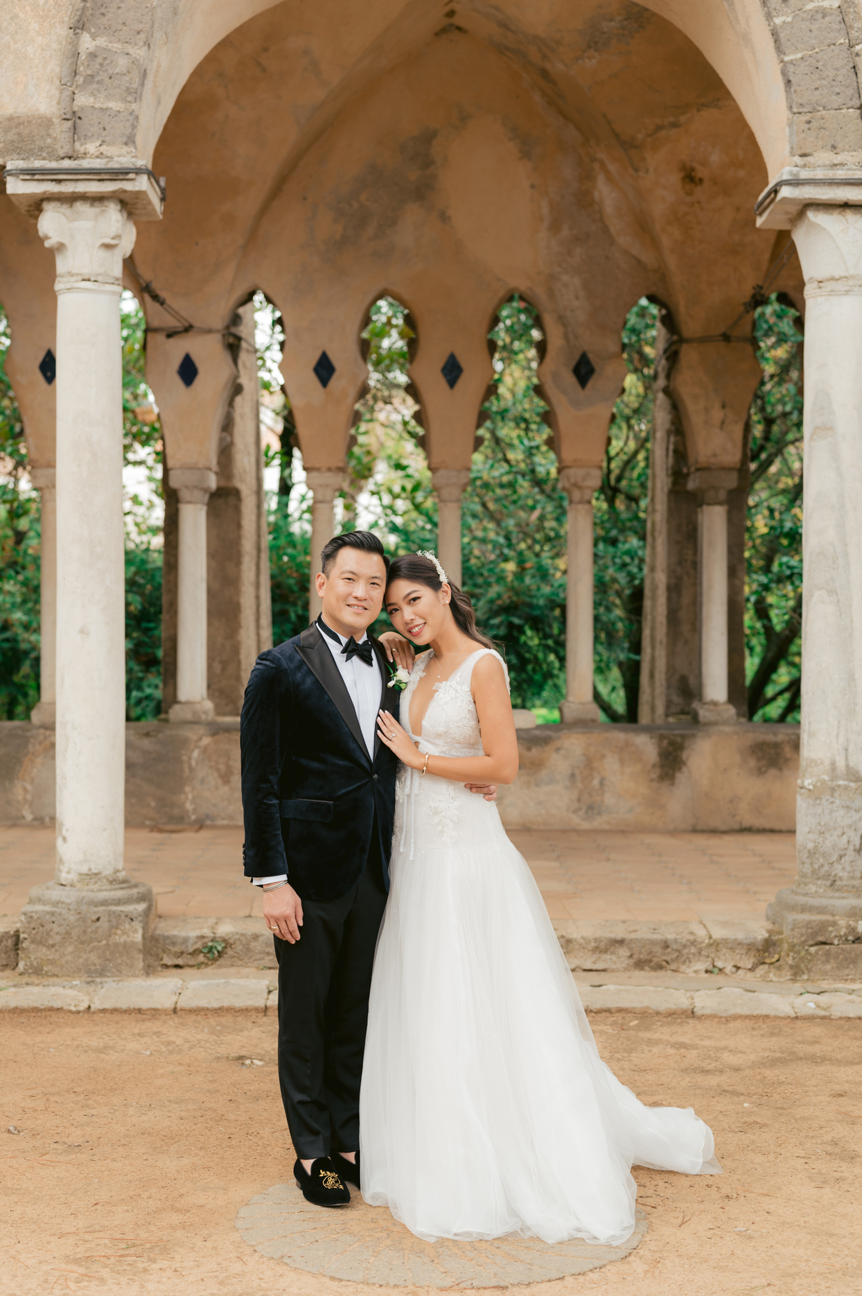 bride and groom stand outside wedding venue