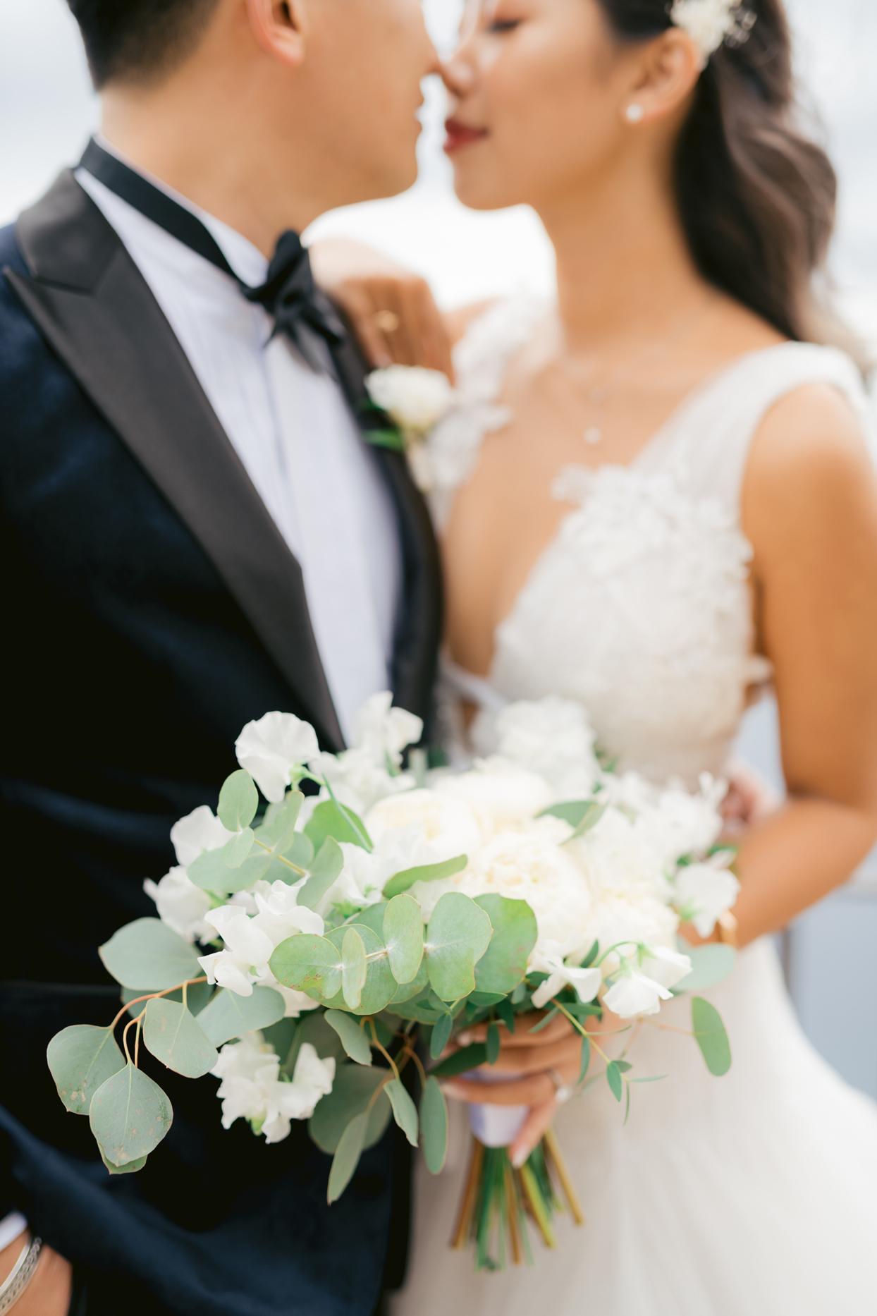 bride and groom embrace holding white floral bouquet