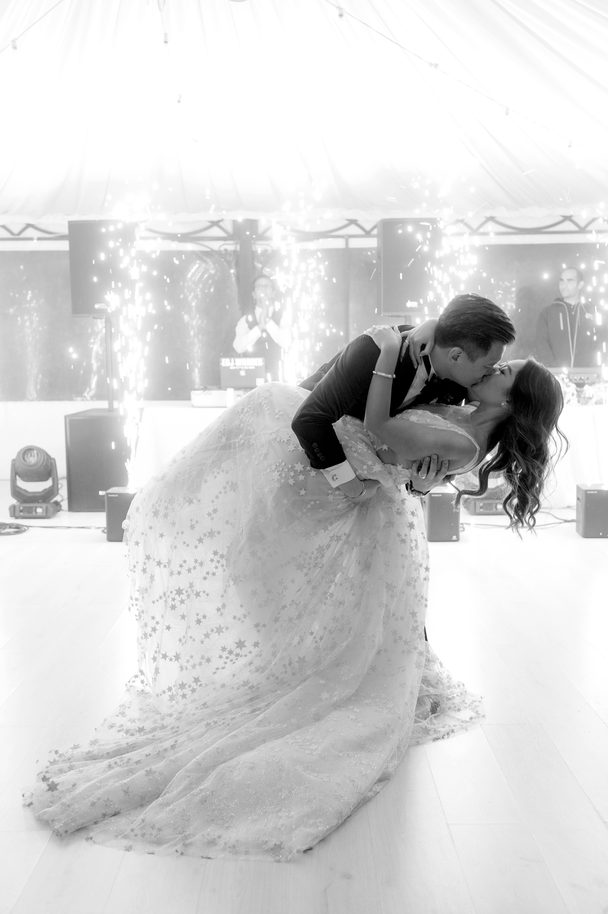 groom dips bride during first dance with sparkler backdrop
