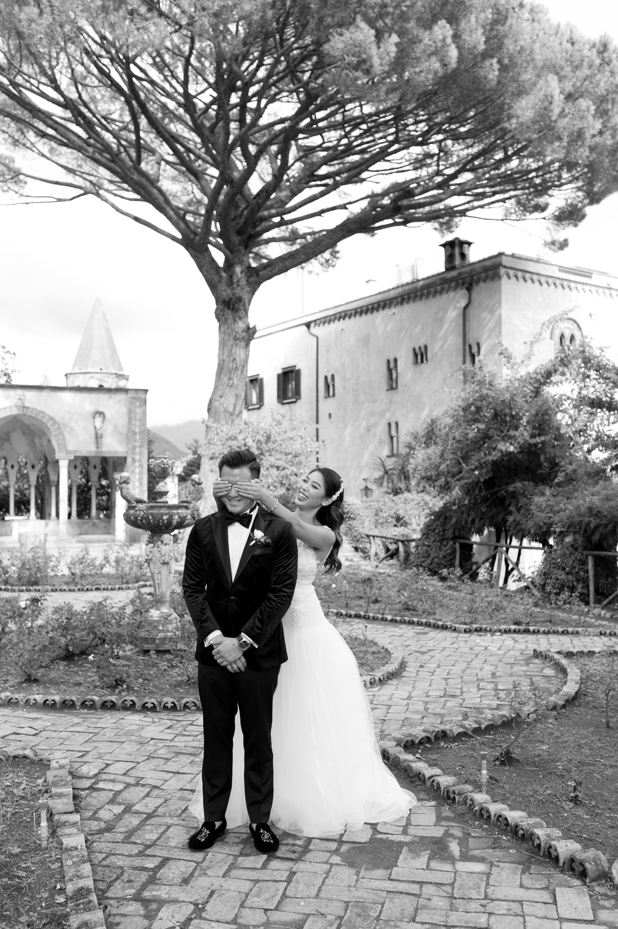 bride stands behind groom covering his eyes before first look