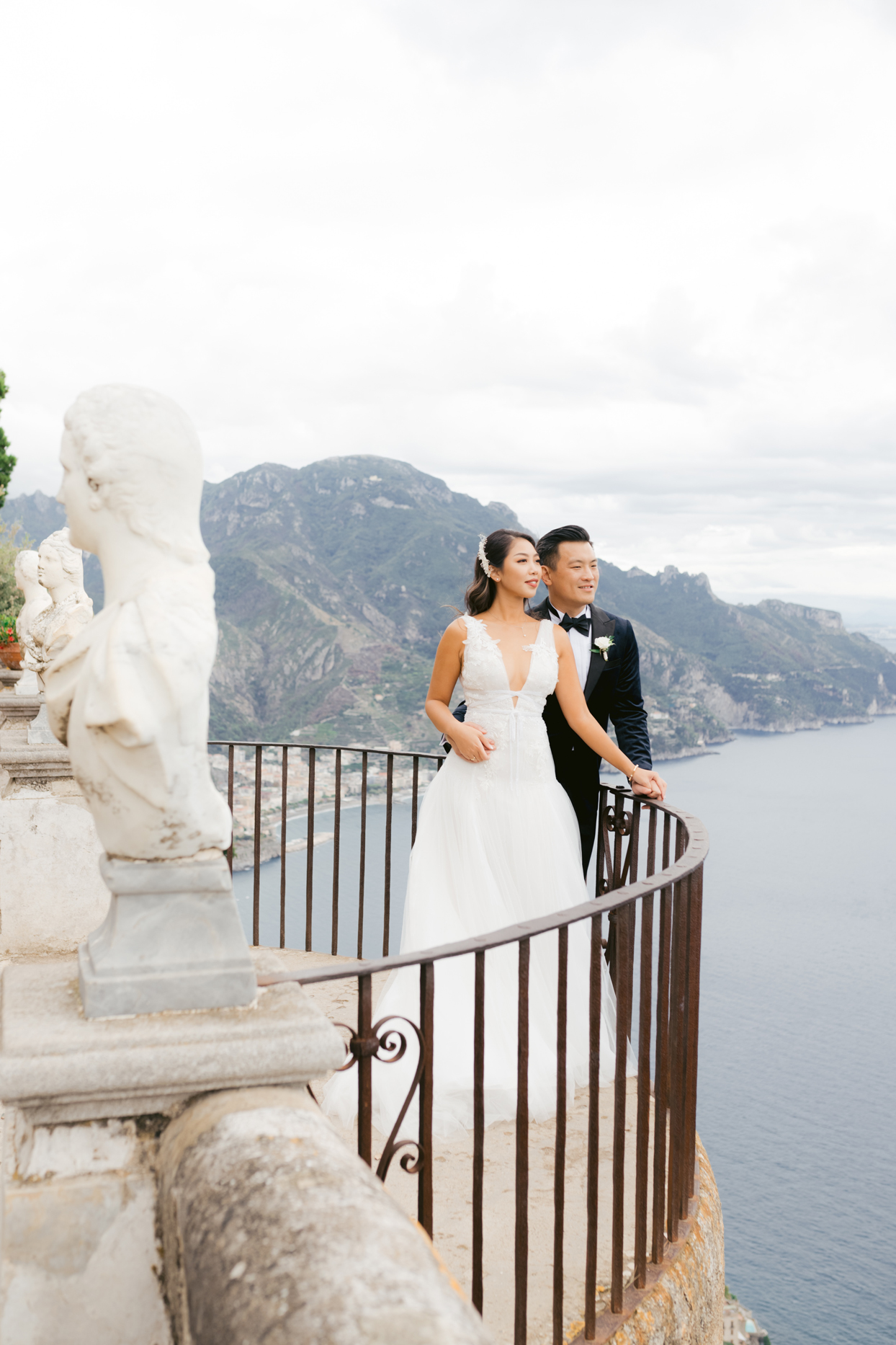 bride and groom share a moment overlooking the water
