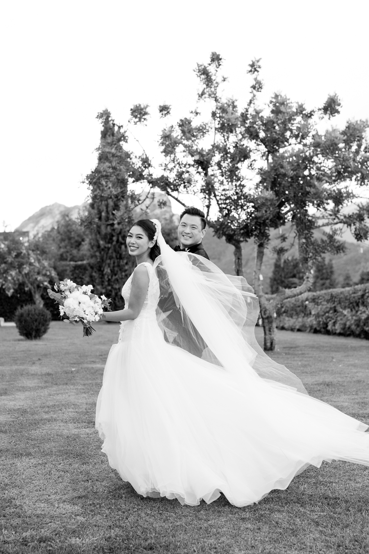 bride and groom smile outside walking away