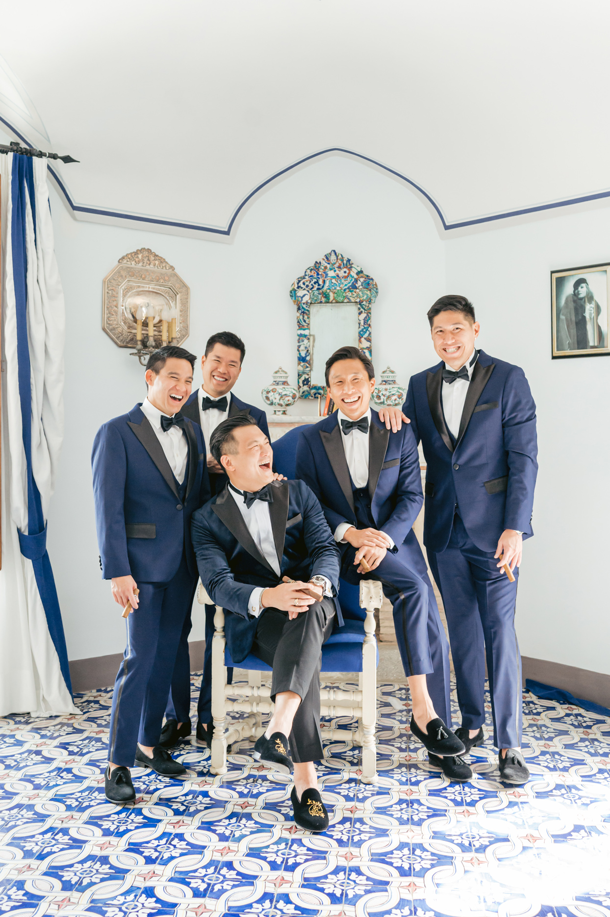 groom smiling with groomsmen wearing navy blue suits