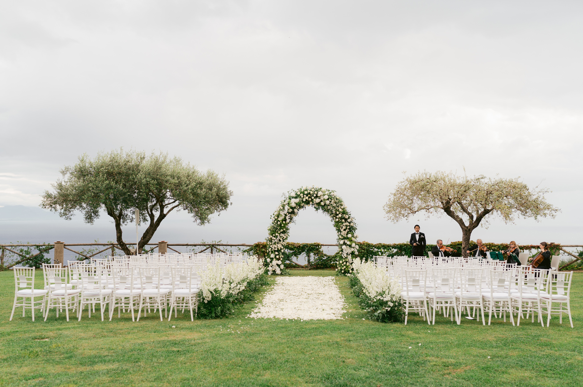 outdoor wedding ceremony with white seating and floral decor