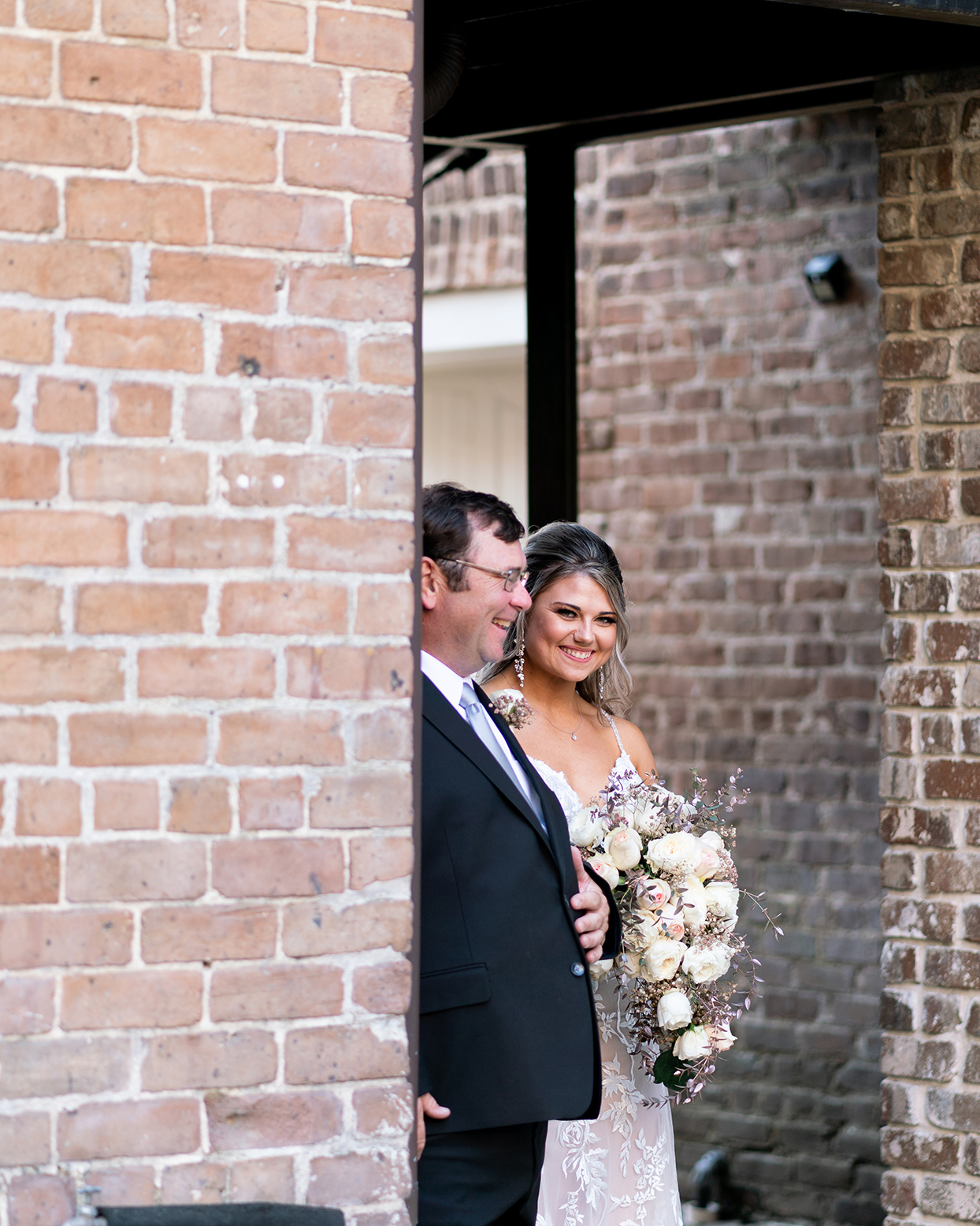 bride and father smiling as they process through stone entryway