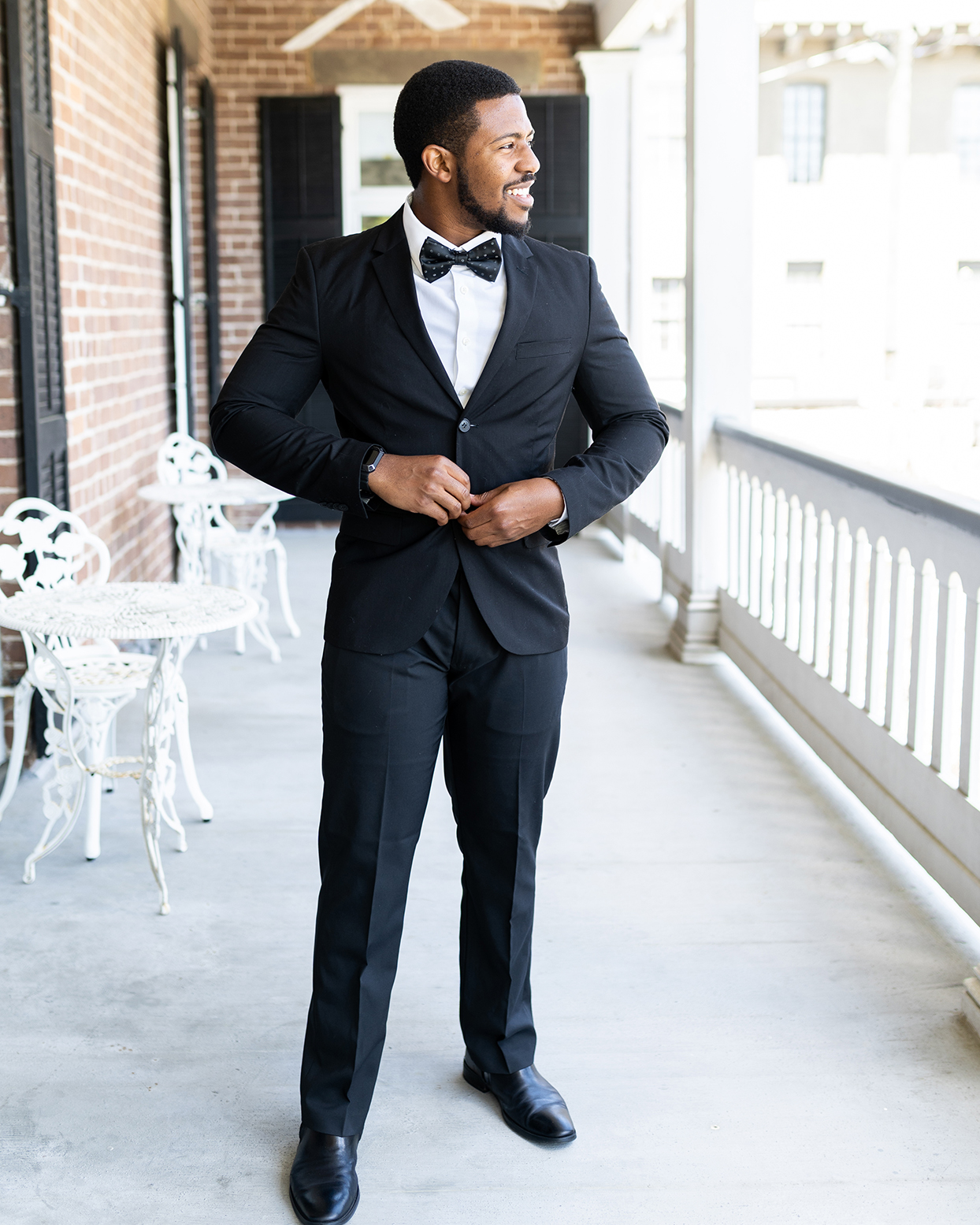 groom in black tux and polka dotted bow tie