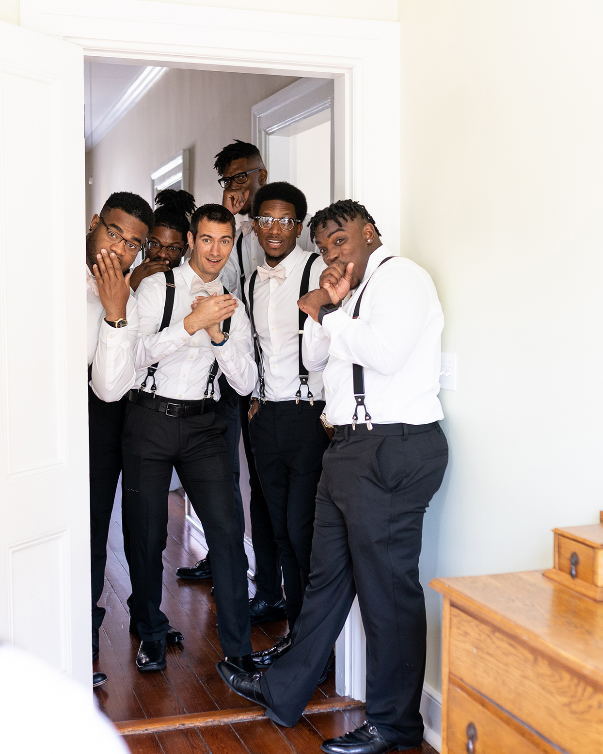 groomsmen in white shirts and black suspenders hanging out in doorway