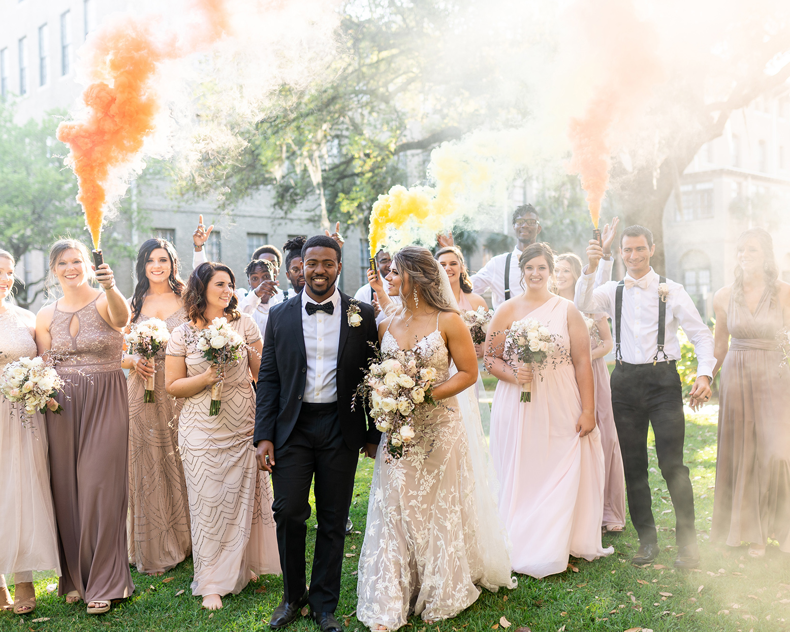 wedding couple walking with wedding party setting off colorful smoke bombs