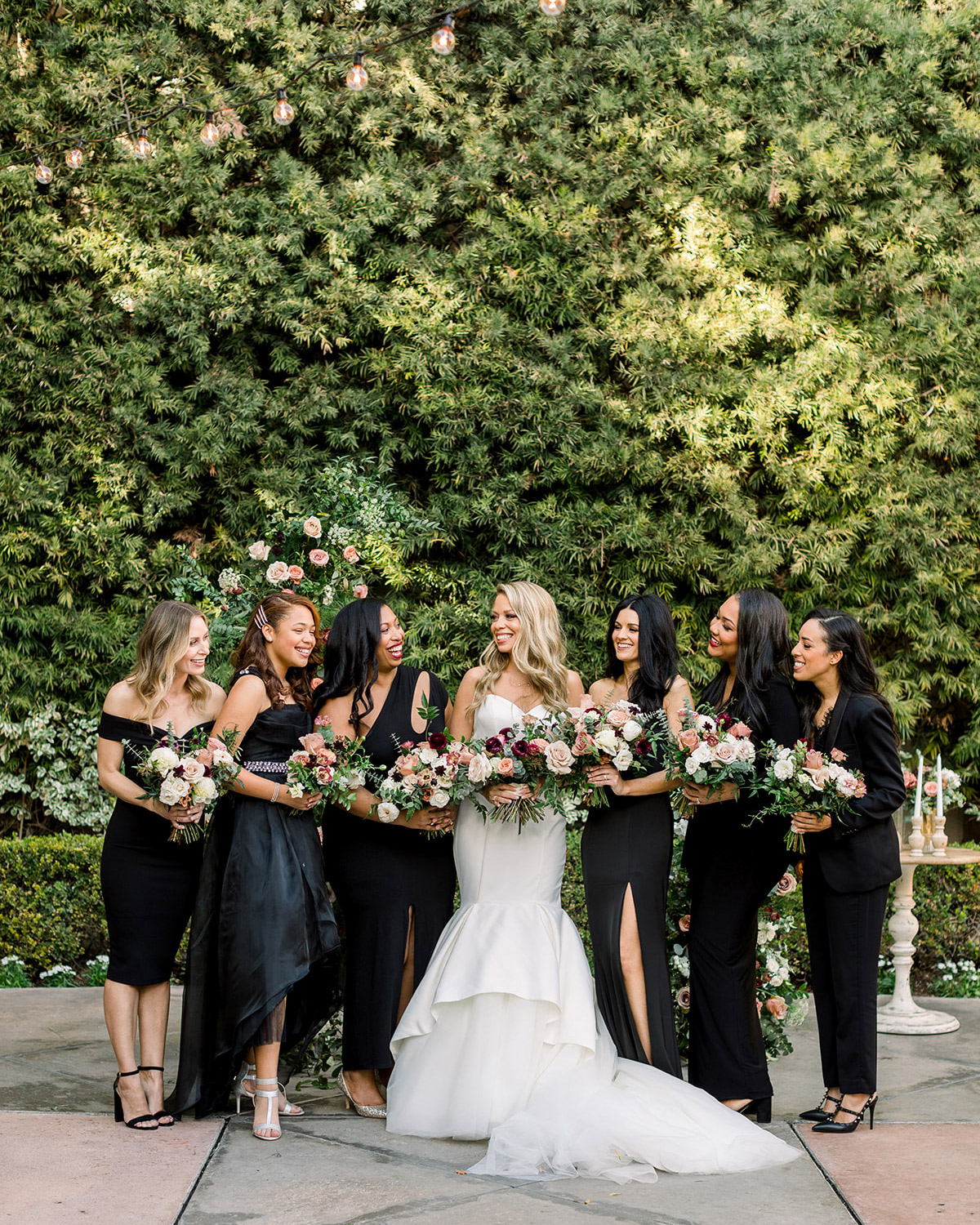 bride and bridesmaids in black against greenery wall