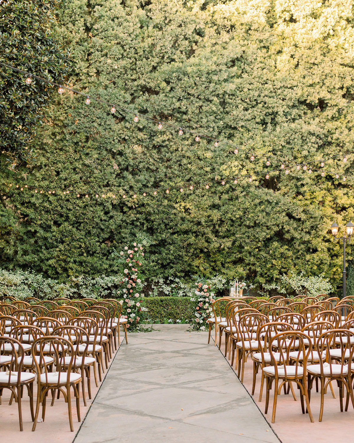 outdoor ceremony location with greenery wall and wooden chairs