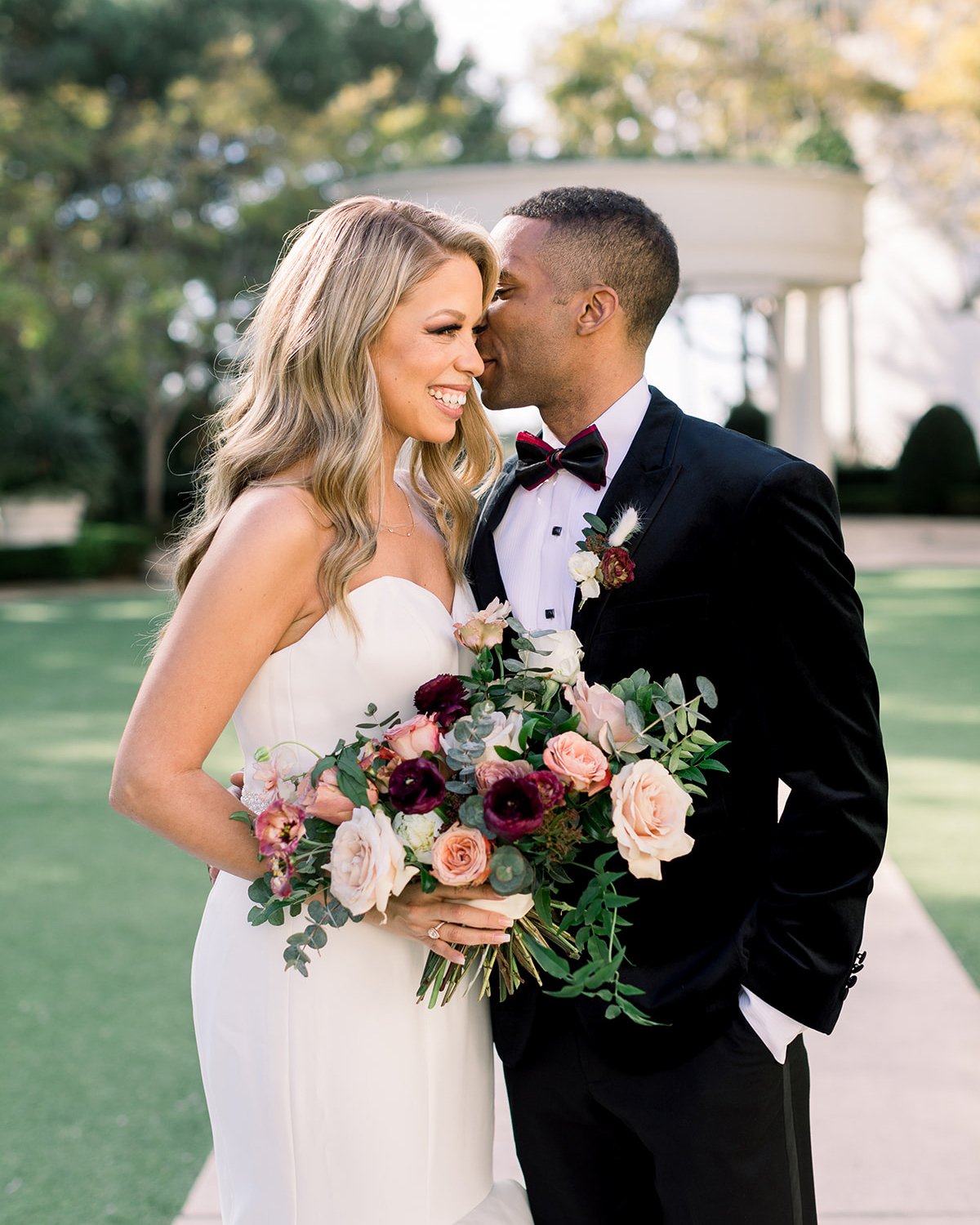 bride and groom posing for portraits with pink floral bouquet