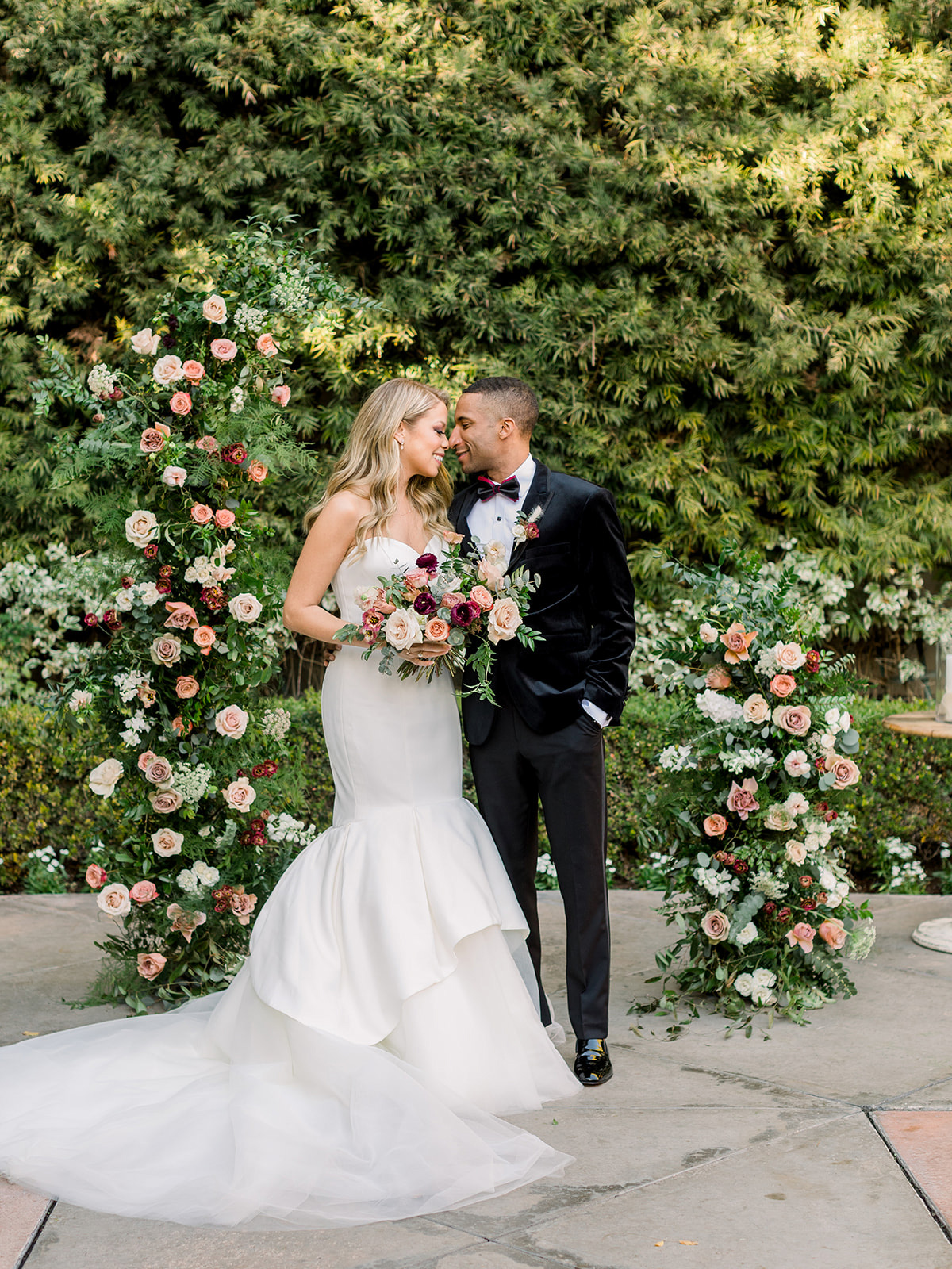 bride in white mermaid wedding dress and groom in black posing for portrait in front of floral arch