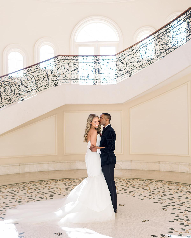 bride and groom posing under elegant stairway