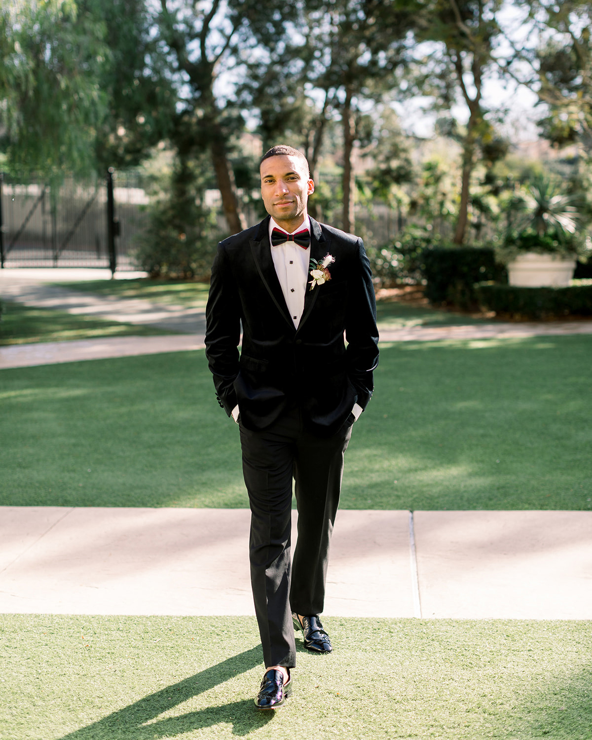 groom in black tux with bowtie with red accents