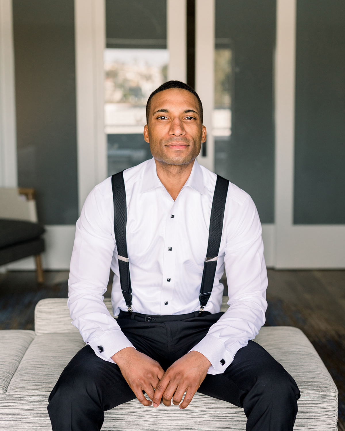 groom sitting in white shirt and black suspenders