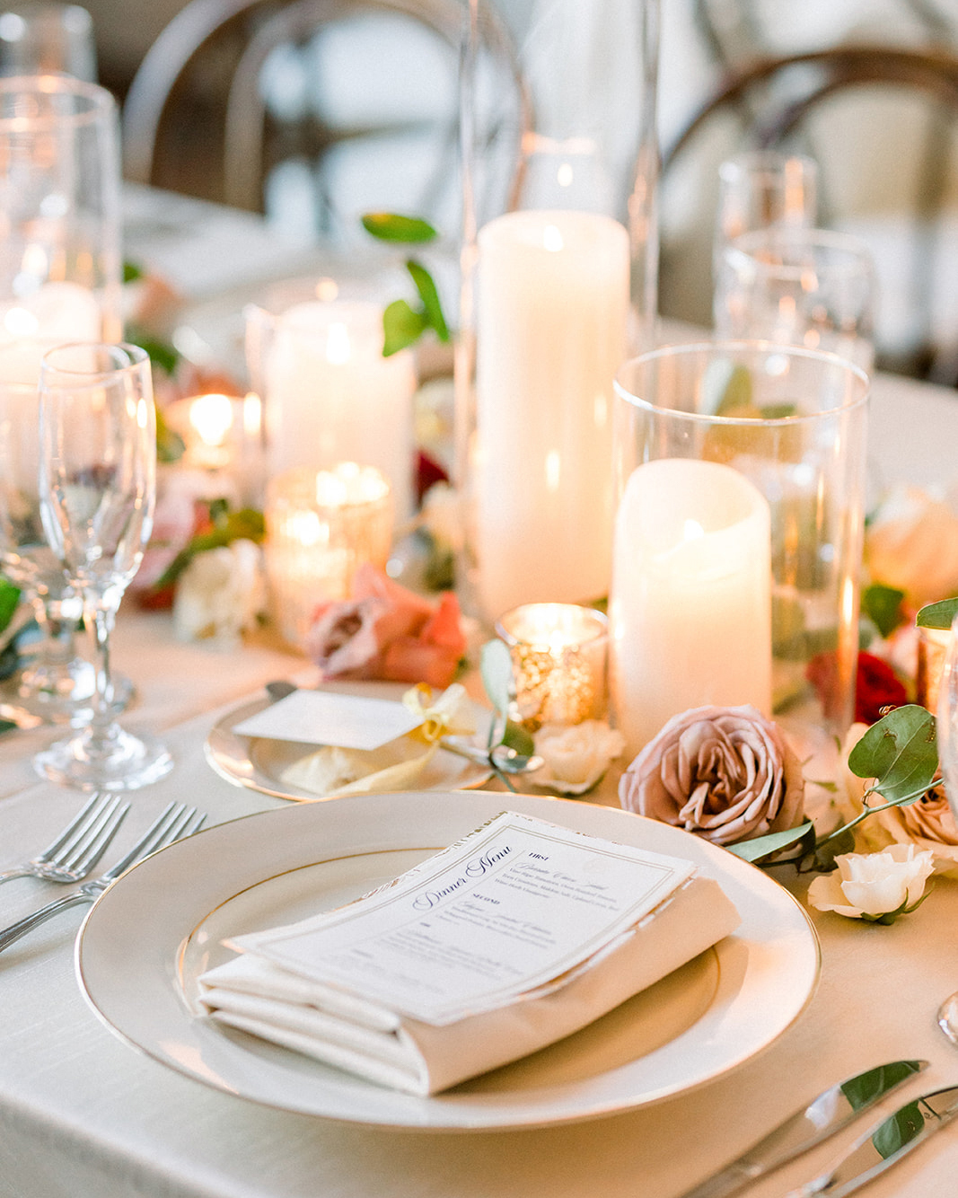 elegant white and gold place setting with berry tone decorations