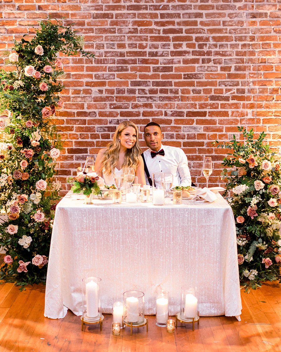 bride and groom sitting at sweetheart table with floral arch