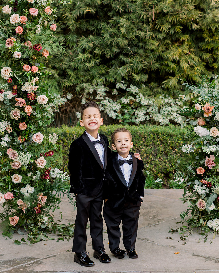 ring bearers in black suits under floral arch