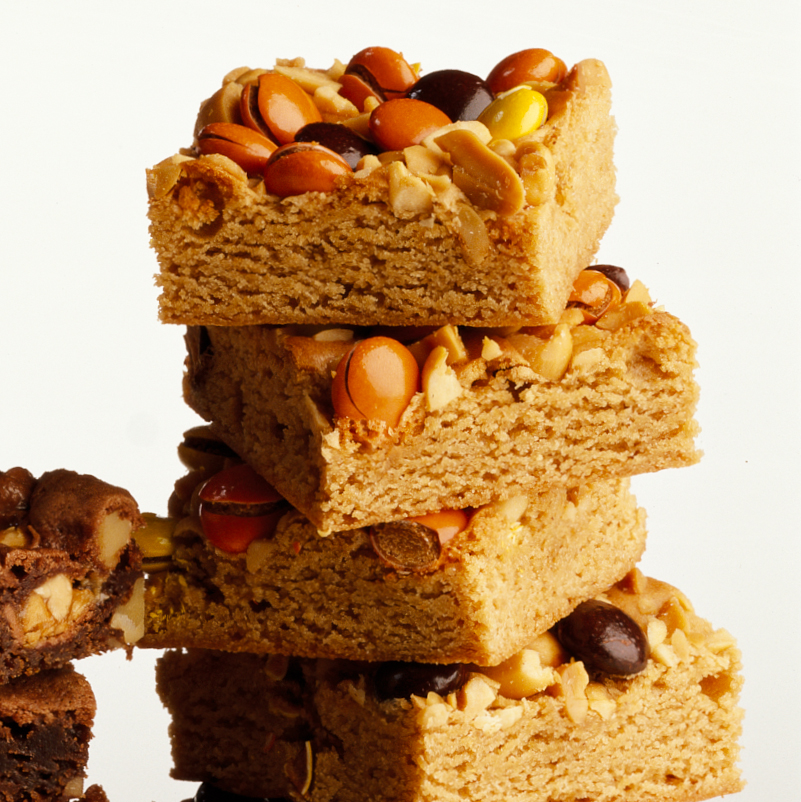 stack of peanut Butter Bars topped with peanuts and candy pieces