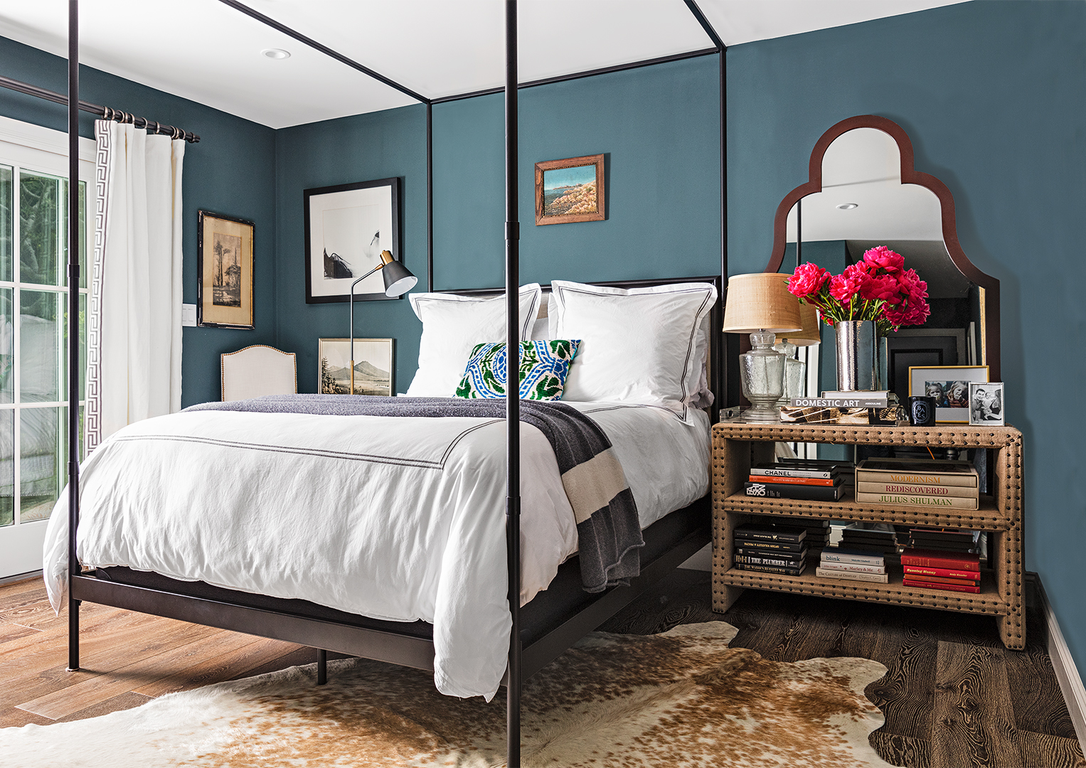blue green master bedroom with rug dark wood accents and white bed sheets