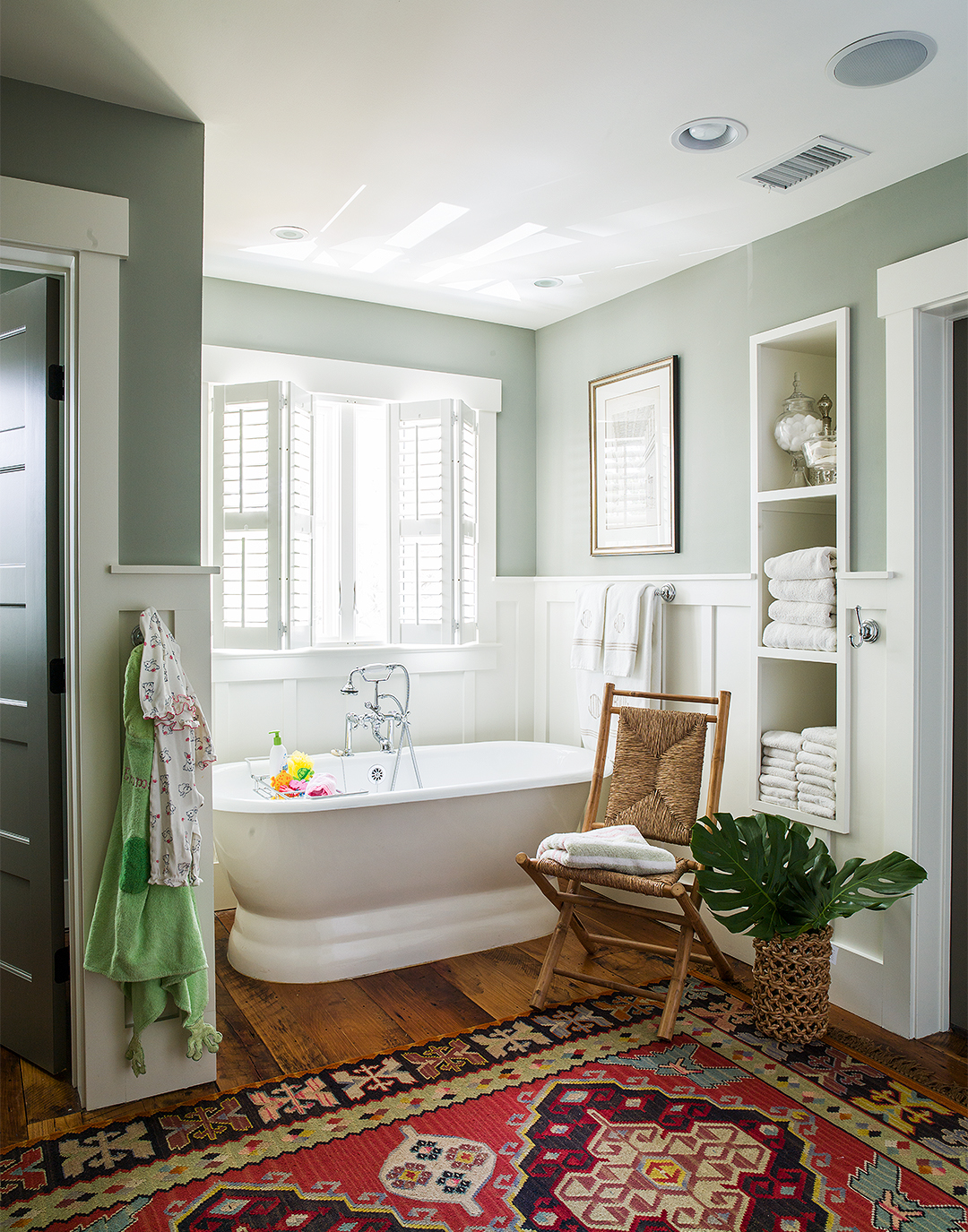 green and white spa bathroom with tub and white towels rug and chair