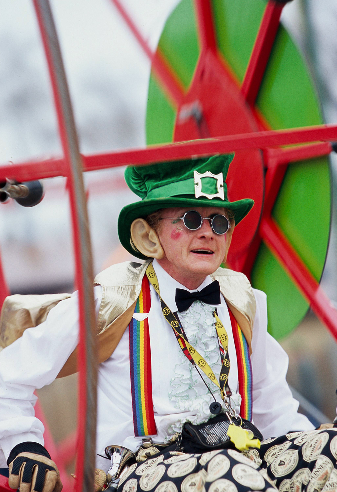 male dressed as leprechaun inside giant red wheel