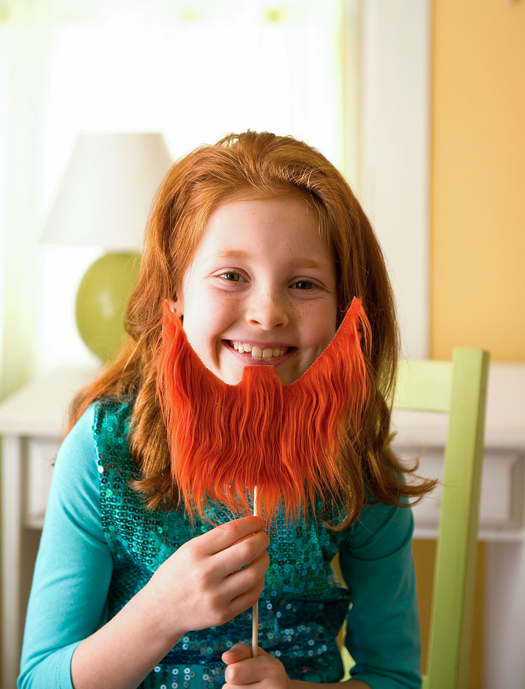 young smiling girl holding diy beard on stick
