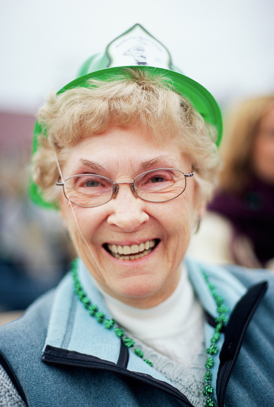 smiling woman wearing green hat and beads in blue jacket