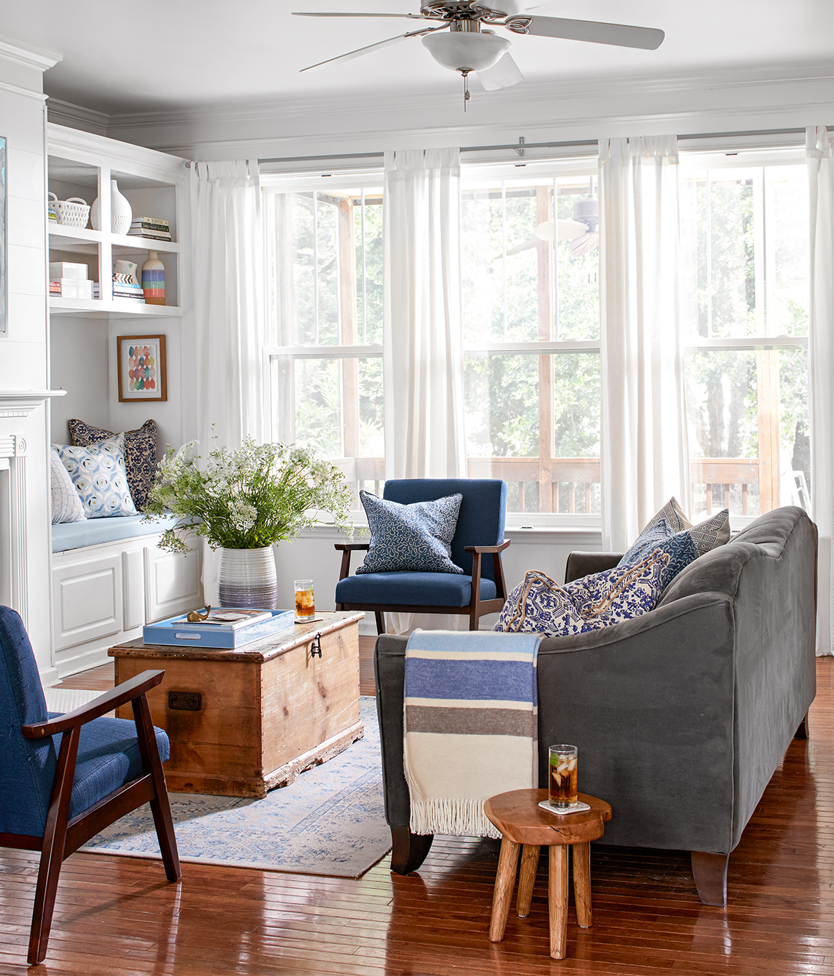 white living room with blue sofa and side chairs and wood chest-style coffee table