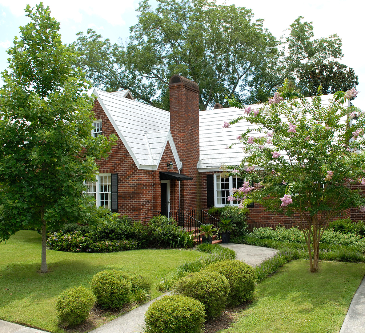 brick house with white roof and trees and bushes