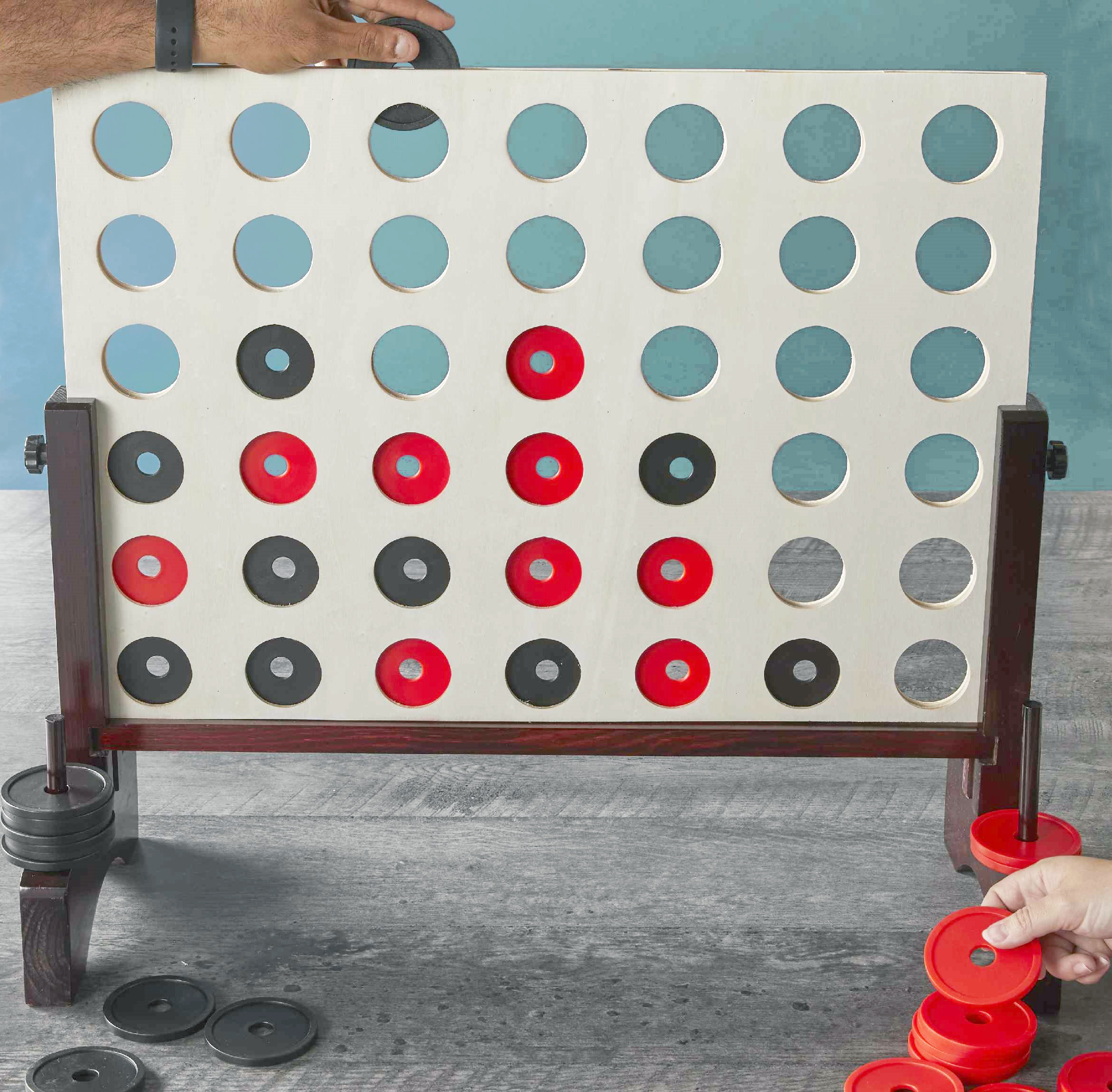 Giant game of connect 4 with two hands adding red and black discs