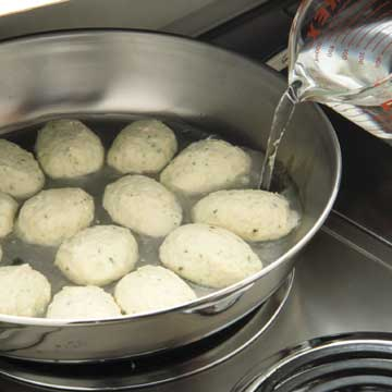 poaching the quenelles by adding salted hot water to skillet