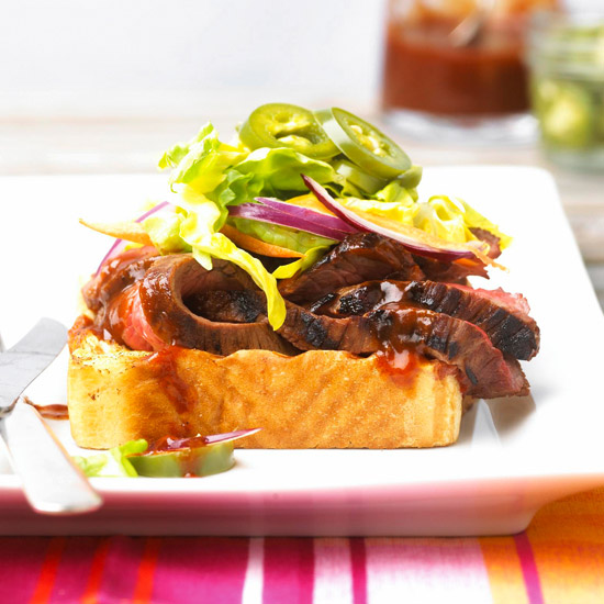 Tri-Tip Steaks with visible grill marks on Texas Toast on white plate. Topped with red onion, jalapeno slices, and shredded lettuce.