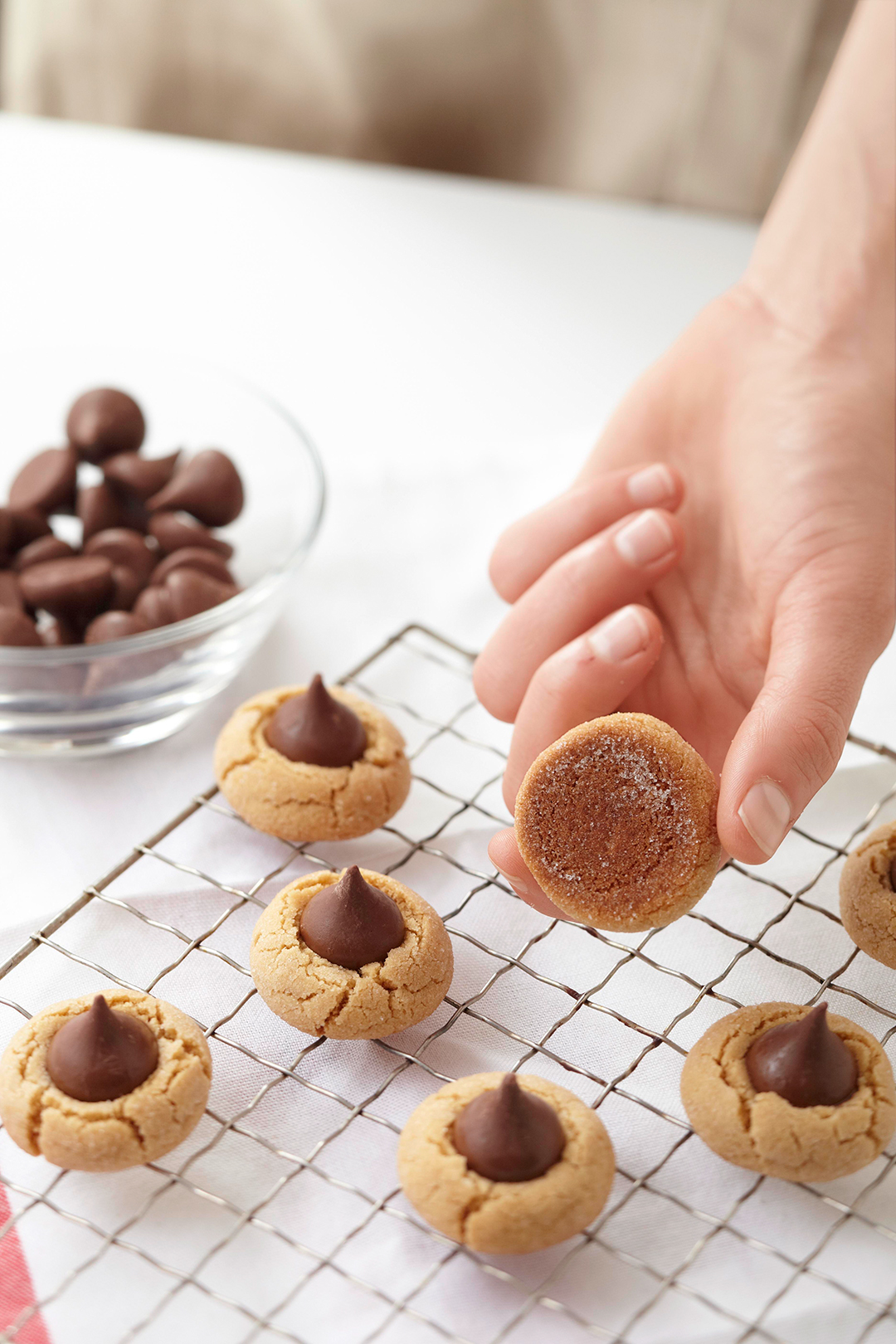 Picking up peanut butter blossom from wire rack to check bottom of cookie for doneness