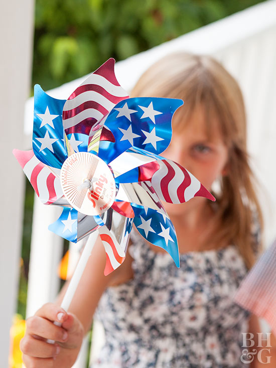 girl holding up 4th of July pinwheel
