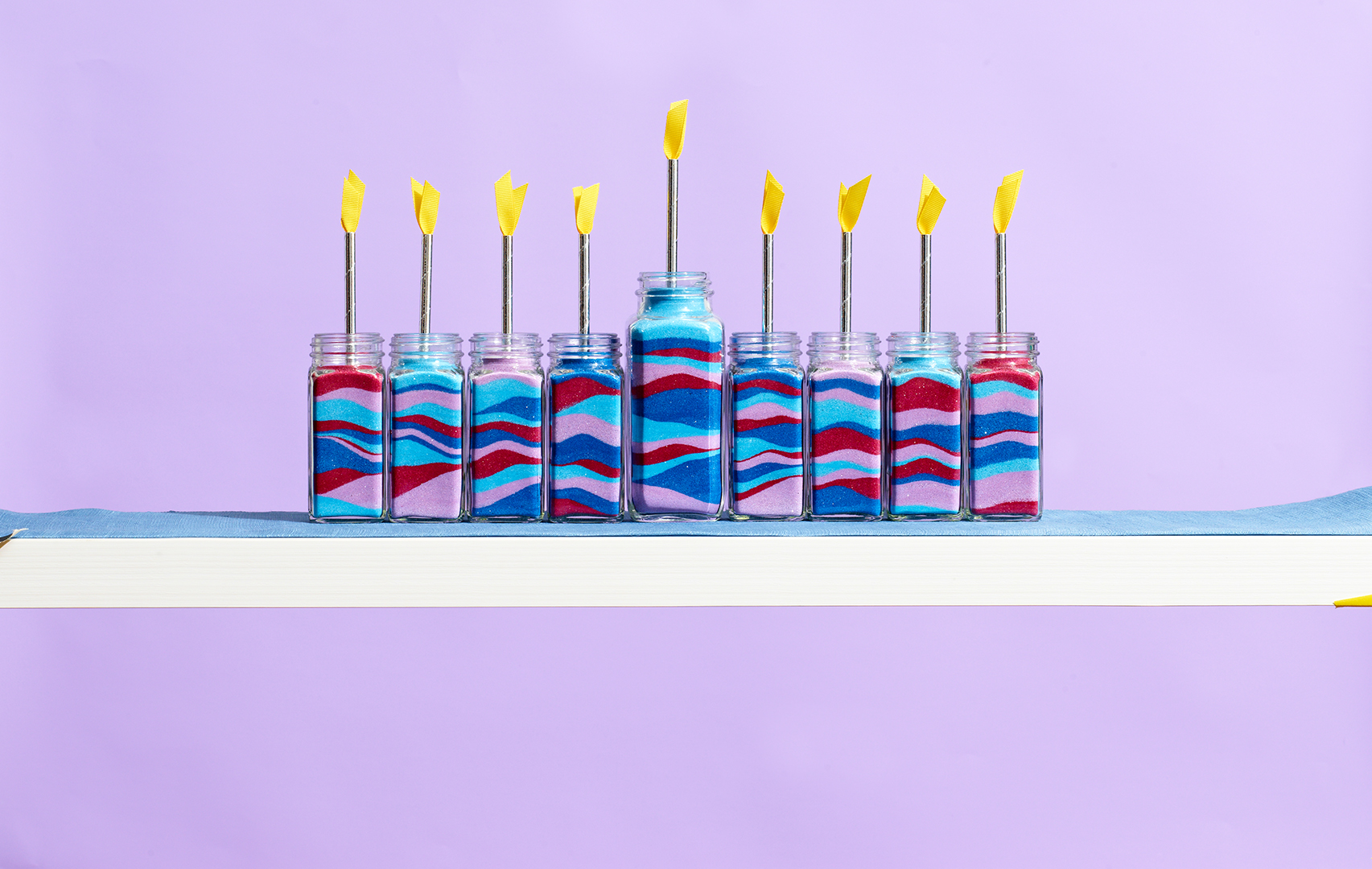 handmade Hanukkah menorahs in multi colored jars on shelf against purple background