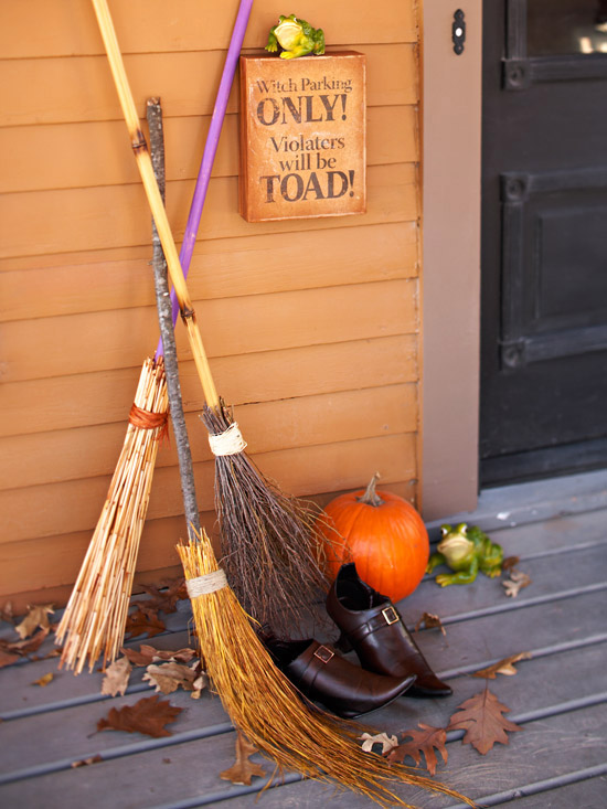 homemade halloween witch brooms next too a front door and an orange wall on a front porch