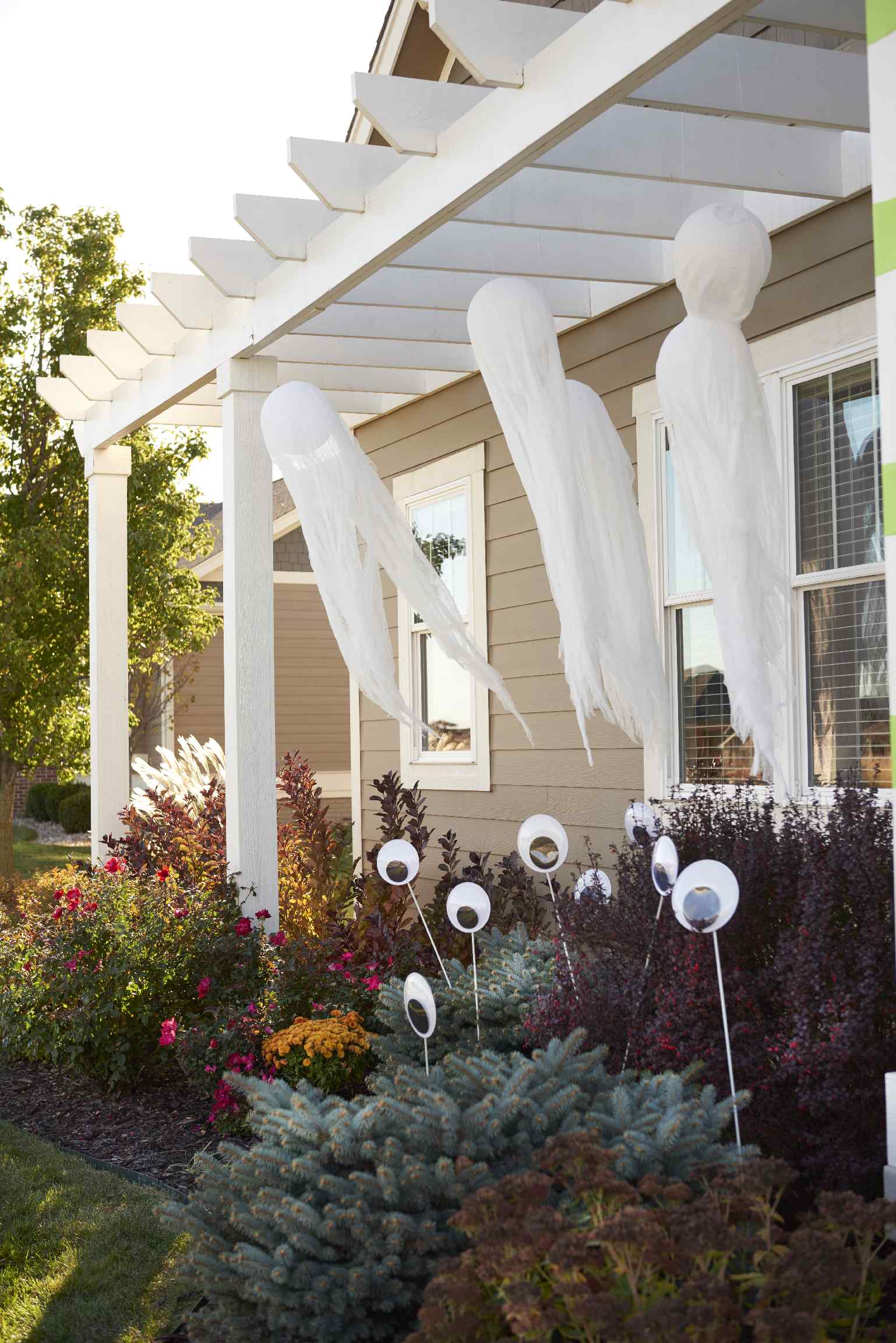 Exterior of a white house at daylight with three cloth ghosts hanging from the front porch