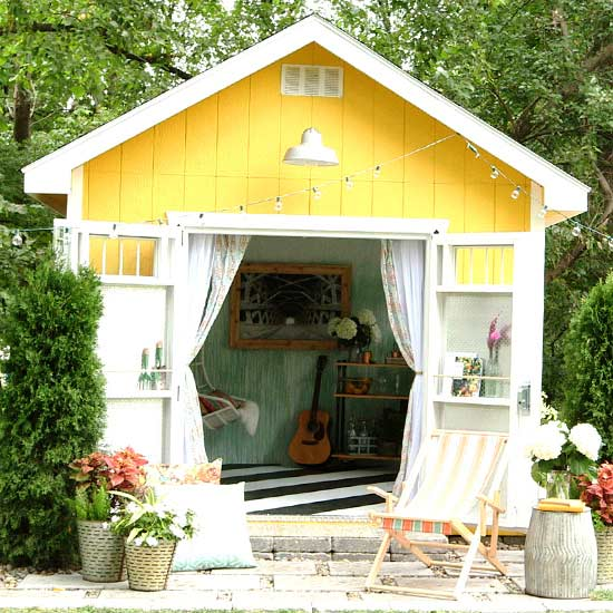 yellow shed with lawn chairs and planters in front