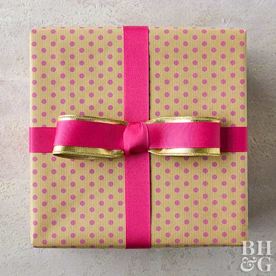 pink and gold ribbon on top of polka dot wrapped gift