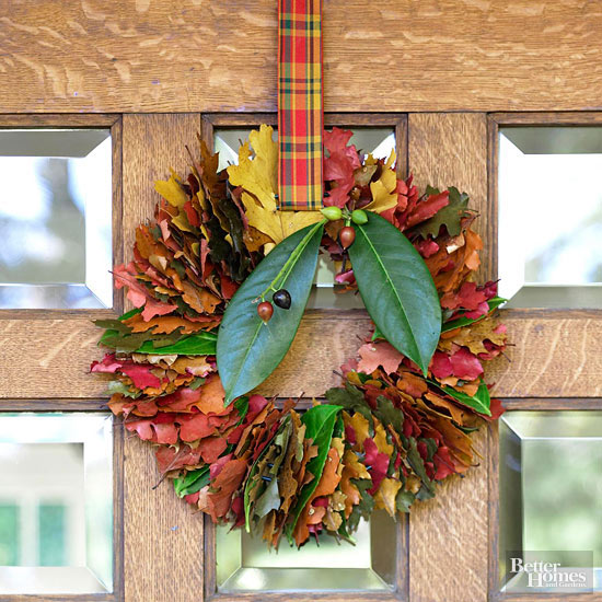 Wreath made of multicolor fall leaves hanging on front door