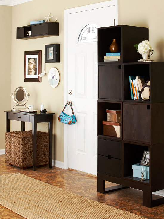 entryway with dark wood cabinets, table and shelves