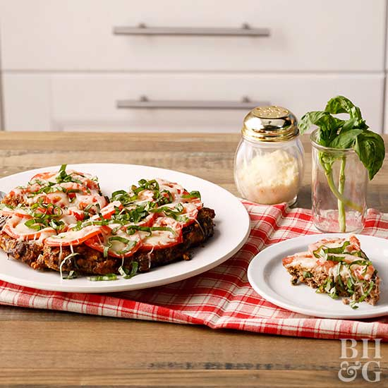 pizza topped meatloaf on plate with sliced tomatoes parmesan and basil on top