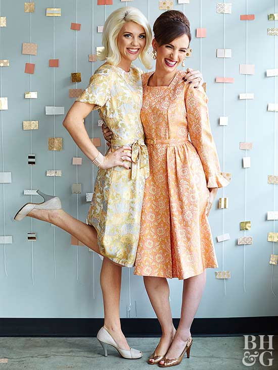two women in retro dresses at party with paper mobiles in background