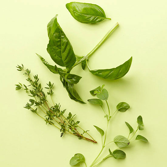 springs of basil, oregano, and thyme on cutting board